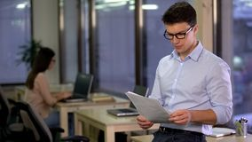 Documento de la lectura del asistente social, analizando indices de desempleo, mercado laboral fotos de archivo libres de regalías