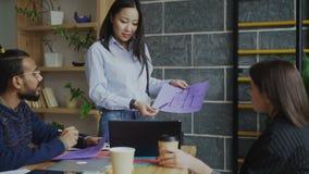 Documento de la mujer asiática joven plan arquitectónico de la casa al equipo étnico multi en oficina de lanzamiento moderna almacen de video