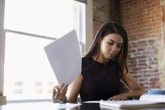 Documento de Making Notes On de la empresaria en oficina Foto de archivo libre de regalías