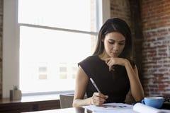 Documento de Making Notes On de la empresaria en oficina Imagenes de archivo