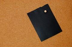 Documento de nota negro sobre tarjeta del corcho Imagen de archivo