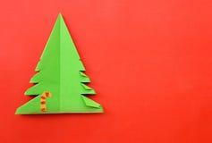 Documento del árbol de navidad de la papiroflexia sobre fondo rojo Imagen de archivo