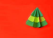 Documento del árbol de navidad de la papiroflexia sobre fondo rojo Fotos de archivo