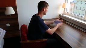 Documento del controllo del giovane nella camera di albergo archivi video
