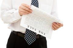 Documento della lettura dell'uomo d'affari con gli annunci di vendite immagini stock libere da diritti