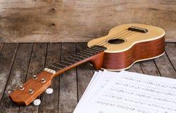 Documento di Chordschart della carta e delle ukulele su fondo di legno Fotografie Stock