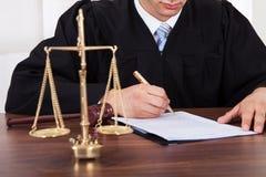 Documento di firma del giudice alla tavola in aula di tribunale Fotografia Stock Libera da Diritti