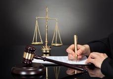 Documento di firma del giudice maschio allo scrittorio immagine stock