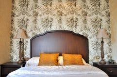 Documento di parete fiorito della camera da letto e mobilia di legno Fotografia Stock
