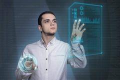 Documento di schermo virtuale commovente del giovane in technol futuristico Fotografie Stock