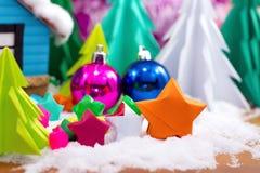 Documento doblado estrella multicolora sobre nieve Imágenes de archivo libres de regalías