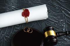 Documento dorato rotto del decreto di divorzio di due fedi nuziali Concetto di separazione e di divorzio immagini stock