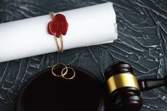 Documento dorato rotto del decreto di divorzio di due fedi nuziali Concetto di separazione e di divorzio fotografia stock