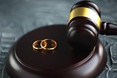Documento dorato rotto del decreto di divorzio di due fedi nuziali Concetto di separazione e di divorzio immagine stock