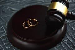 Documento dorato rotto del decreto di divorzio di due fedi nuziali Concetto di separazione e di divorzio immagini stock libere da diritti