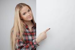 Documento en blanco blanco sonriente joven y demostraciones del control rubio de la muchacha del adolescente sobre él Imagen de archivo
