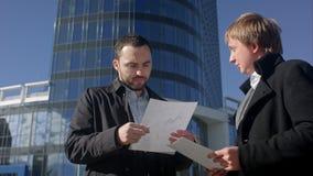 Documento en blanco del rasgón del hombre de negocios sobre el encuentro al aire libre almacen de metraje de vídeo