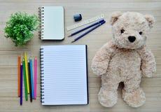 Documento en blanco, pintura del color y muñeca del oso sobre el v tablero de madera Foto de archivo