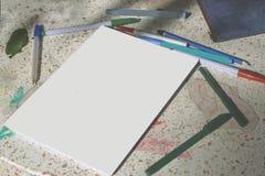 Documento en blanco sobre la tabla de piedra con las plumas del color para el negocio, educatio foto de archivo