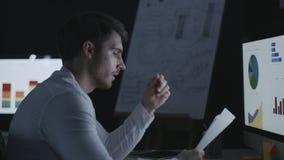 Documento enojado del documento del hombre de negocios que lanza sobre la tabla del ordenador en oficina oscura almacen de video