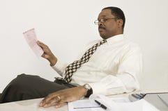 Documento finanziario della lettura del consulente in ufficio Fotografie Stock Libere da Diritti