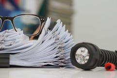 Documento inacabado, pilas de ficheros de papel con los clips en el escritorio para el informe, vidrios y linterna Imagen de archivo