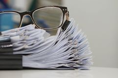 Documento inacabado, pilas de ficheros de papel con los clips en el escritorio para el informe y vidrios Fotografía de archivo