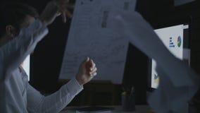 Documento malvado de los datos del hombre de negocios que lanza en la tabla del ordenador en oficina oscura almacen de metraje de vídeo