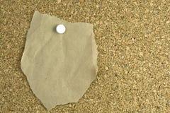 Documento marrón rasgado sobre corcho-tarjeta Fotografía de archivo