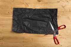 Documento negro arrugado sobre fondo de madera con las tijeras imagenes de archivo