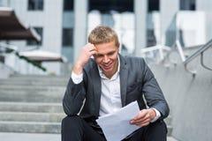 Documento novo feliz da leitura do homem de negócios Fotos de Stock Royalty Free