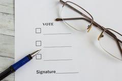 Documento per il voto sulla tavola di legno, accanto alla penna ed ai vetri immagini stock libere da diritti