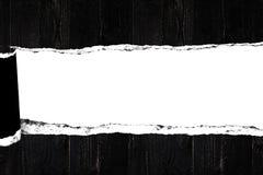 Documento rasgado sobre el fondo de madera negro del tablón para el diseño del texto del anuncio Imagen de archivo libre de regalías