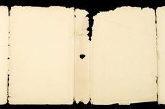 Documento rasgado viejo sobre fondo negro Fotografía de archivo libre de regalías