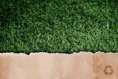Documento reciclado sobre hierba. Fotografía de archivo libre de regalías