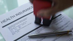 Documento rifiutato di politica dell'assicurazione malattia, guarnizione dei bolli della mano su carta ufficiale archivi video