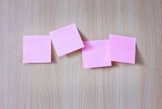 Documento rosado del post-it sobre el tablero de madera Fotografía de archivo libre de regalías