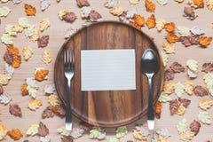 Documento sobre plato con las hojas de arce en el fondo de madera Imagenes de archivo