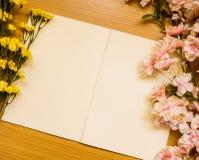 Documento y flores sobre la tabla de madera Imágenes de archivo libres de regalías