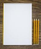 Documento y lápices sobre la tabla de madera fotos de archivo