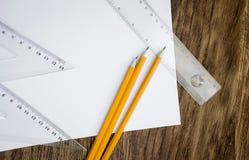 Documento y lápices sobre la tabla de madera Fotografía de archivo