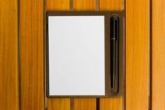 Documento y pluma sobre una madera. Fotos de archivo