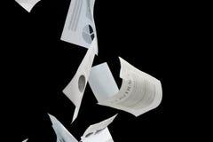 Documentos comerciales que caen abajo sobre fondo negro Foto de archivo