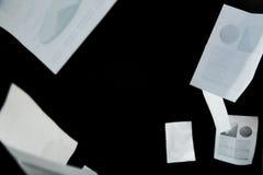 Documentos comerciales que caen abajo sobre fondo negro Imagenes de archivo