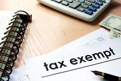 Documentos con el título exento de impuestos en una tabla fotos de archivo libres de regalías