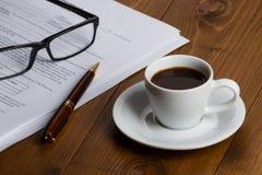 Documentos con la pluma, los vidrios y la taza de café Fotografía de archivo libre de regalías