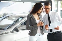 Documentos de firma de la mujer joven en la concesión de coche con el vendedor Imágenes de archivo libres de regalías
