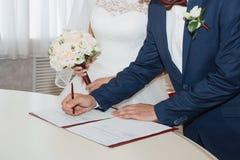 Documentos de firma de la boda de los pares jovenes Imagen de archivo libre de regalías
