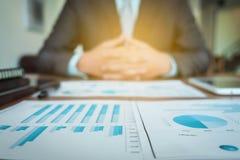 Documentos de negocio en la tabla de la oficina con el diagrama financiero del gráfico Imagen de archivo libre de regalías