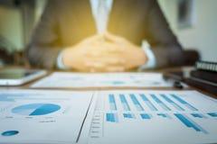 Documentos de negocio en la tabla de la oficina con el diagrama financiero del gráfico Foto de archivo